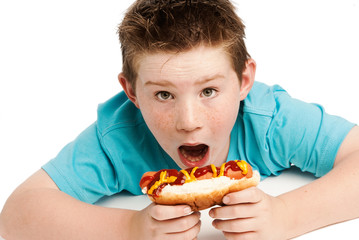 Hungry young boy eating a hotdog.