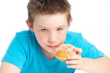 Youny boy eating a sugary doughnut.