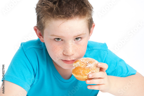 Youny boy eating a sugary doughnut.