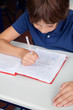 Little Schoolboy Reading Book At Desk