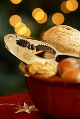 Nutcracker and nuts in a bowl with Christmas lights