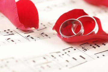 Two rings on music notes with red rose petals.