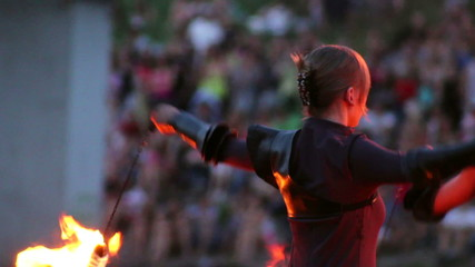 Flame artist perform using burning chain fire pois and sticks