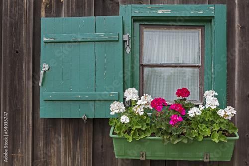 Kleines Fenster an einer Berghütte mit Geranien