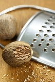 Close-up of nutmeg and grater on wooden background.