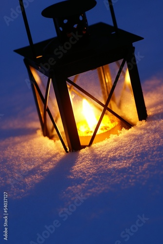 Lantern with burning candle on snow in the evening.