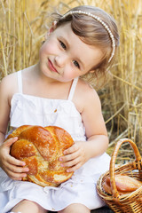 happy baby girl on field of wheat with bread