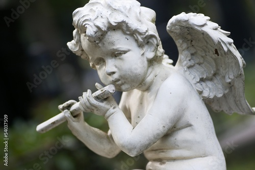 Statue of a little angel on cementery.