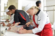 Girl cutting meat during butcher training course - 54038128