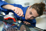 Young student in bodywork changing car windshield