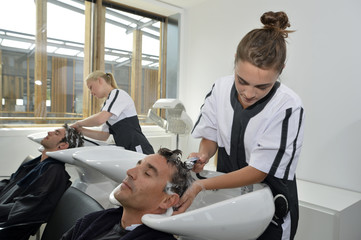 Young women in hair salon washing customer's hair