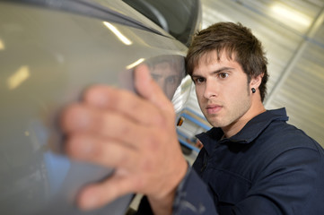 Coachbuilding student working on automobile in garage