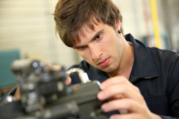 Teenager in professional training, repairing bike engine
