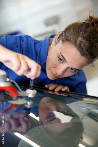 Leinwanddruck Bild Young student in bodywork changing car windshield