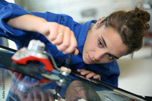 Young student in bodywork changing car windshield - 54038191