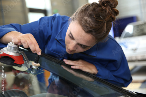 Young student in bodywork changing car windshield - 54038195