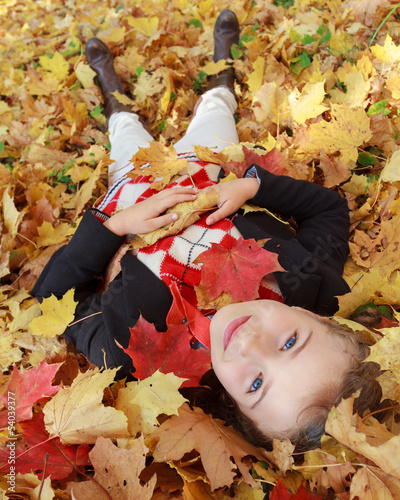Autumn fun - lovely girl playing in autumn park