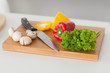 Chopping board in a kitchen with red and yellow pepper