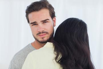 Woman giving hug to uninterested boyfriend
