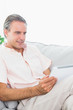 Happy man relaxing on his couch using tablet pc