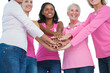 Happy women wearing breast cancer ribbons with hands together