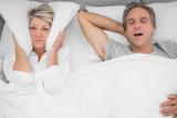 Man snoring loudly as partner blocks her ears