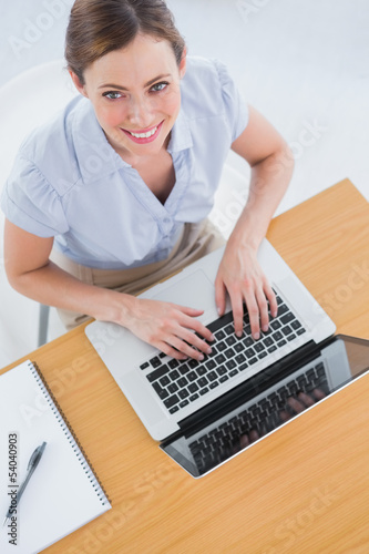 Businesswoman typing on her laptop and smiling up at camera