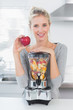 Pretty woman leaning on her juicer full of fruit and holding red