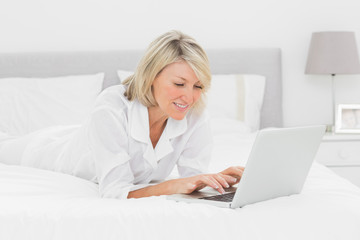 Smiling woman using her laptop on her bed
