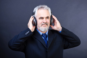 Studio shot of  business man with headphones listening music on
