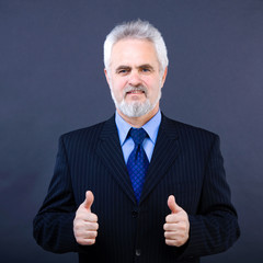 Studio shot of  business man showing thumbs up sign on the dark