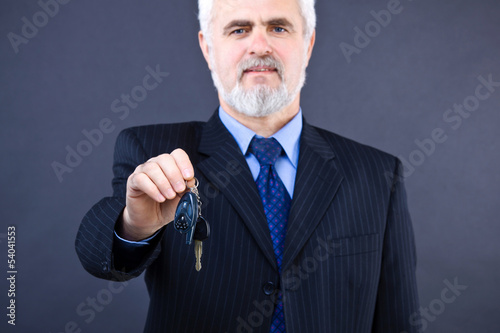 Studio shot of  business man with keys of car on the dark backgr