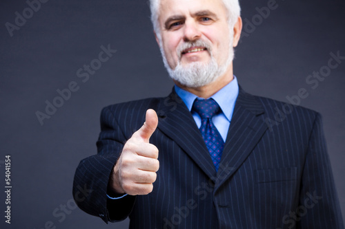 Studio shot of  business man showing thumb up sign on the dark b
