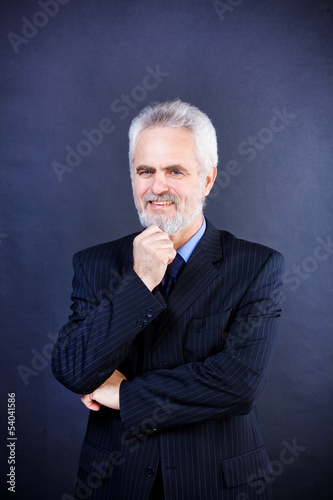 Studio shot of a smiling business man with crossed arms on the d