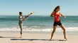 Two women doing martial arts on the beach