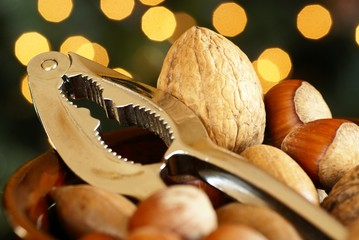 Nutcracker and nuts in a bowl with Christmas lights background.