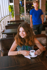 Young girl waiting for a boyfriend in cafe
