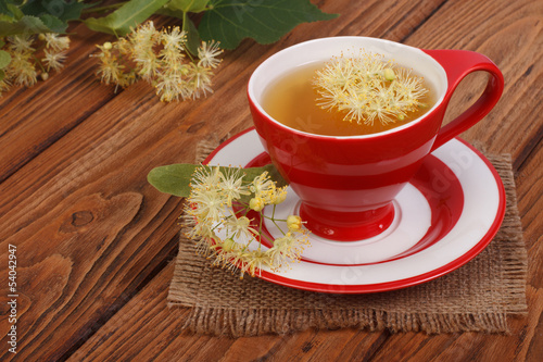 Herbal tea with linden flowers on a brown wooden table