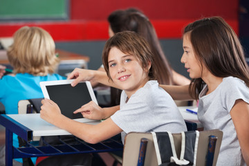 Boy With Girl Using Digital Tablet At Desk