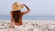 Beautiful brunette with hat tanning and looking at the sea
