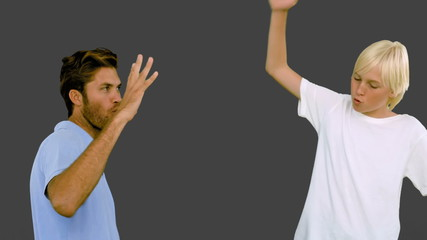 : Father and son hitting their fists together on grey background