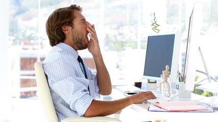 Businessman yawning at his desk