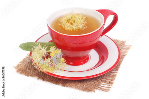 Tea with a linden in a red cup on a napkin isolated on white