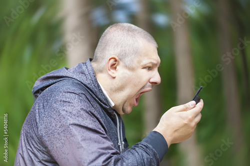 Angry man screaming in phone on the rotating background