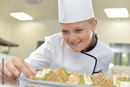 Młody żywieniowiec przygotowywa tacę zakąski