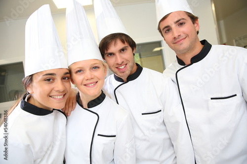 Team of future restaurant chefs looking at camera - 54048386