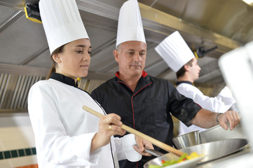 Chef teaching student how to prepare wok dish