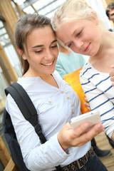 Girlfriends websurfing on smartphone at school