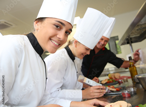 Team of young chefs preparing delicatessen dishes
