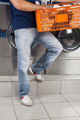 Man Holding Basket Of Clothes In Laundry
